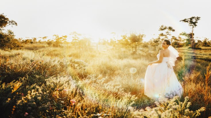 A bride in a field at a destination wedding location.