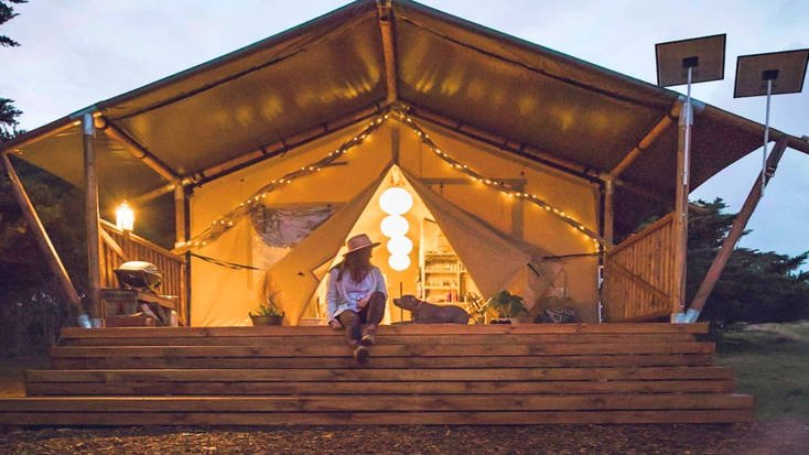 A woman and dog sitting outside a safari tent rental on Phillip Island near Melbourne.