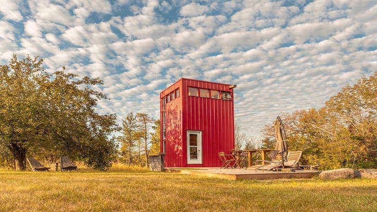 Red tiny house rental in a field in Canada for where to travel this winter.