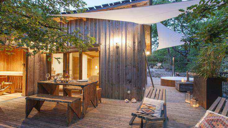 Private deck of a tree house in France with a picnic table and hot tub for where to travel this winter.
