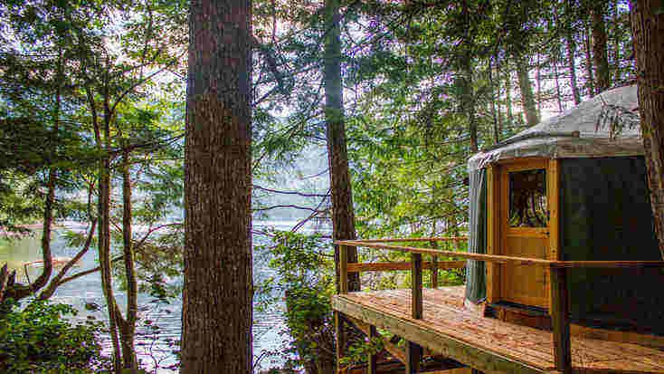 Yurt camping rental on a raised deck overlooking a river through the trees.