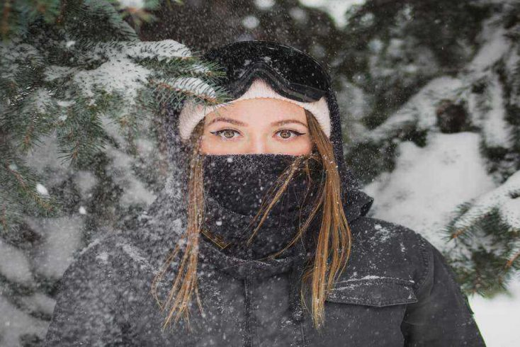 Image of girl wearing some of the best winter essentials for outdoor luxury camping