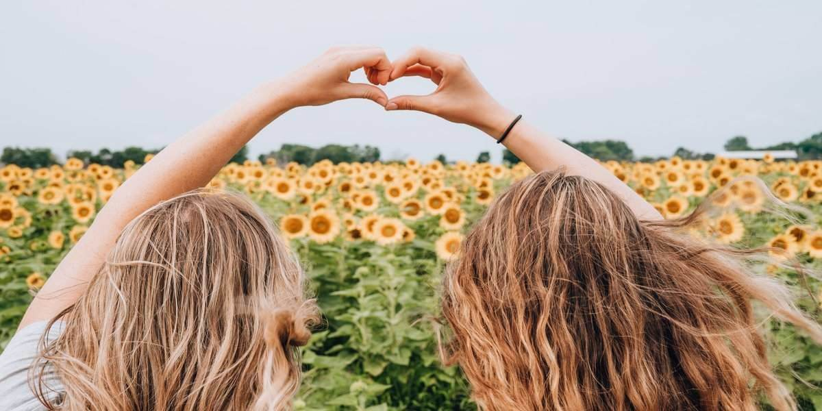 Two women in a field of sunflowers, single on Valentine's Day