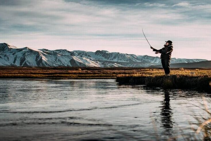 man fishing by lake after learning how to fish