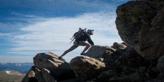 man climbing rocks in Julian, California during trip