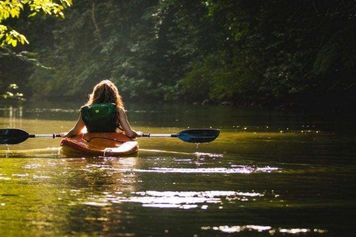 Woman kayaking during glamping washington trip for long weekends 2020 luxury camping