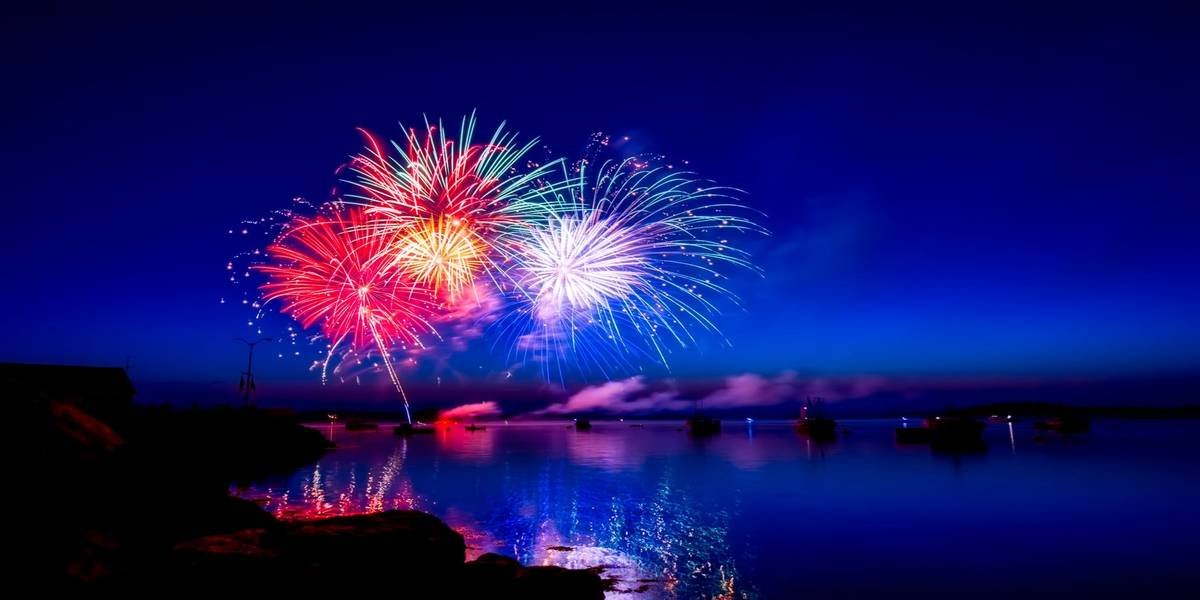 Fireworks in the night sky over a river and boats