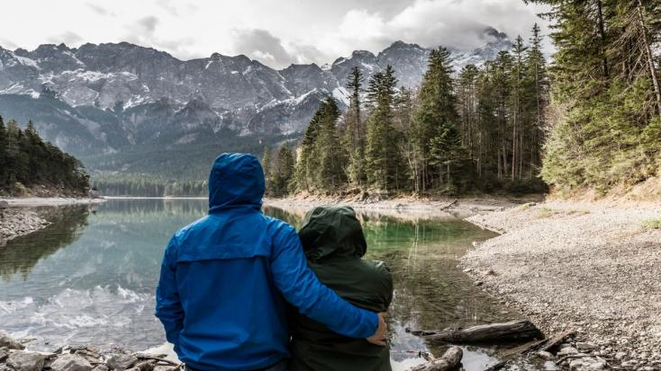 A man and woman looking out over a mountain lake on a romantic Valentine's Day getaway.
