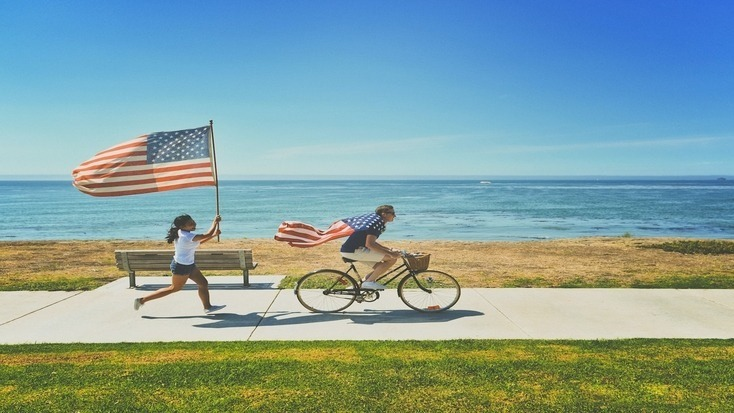 A man and woman with the American Flag in one of the best places to go for 4th July