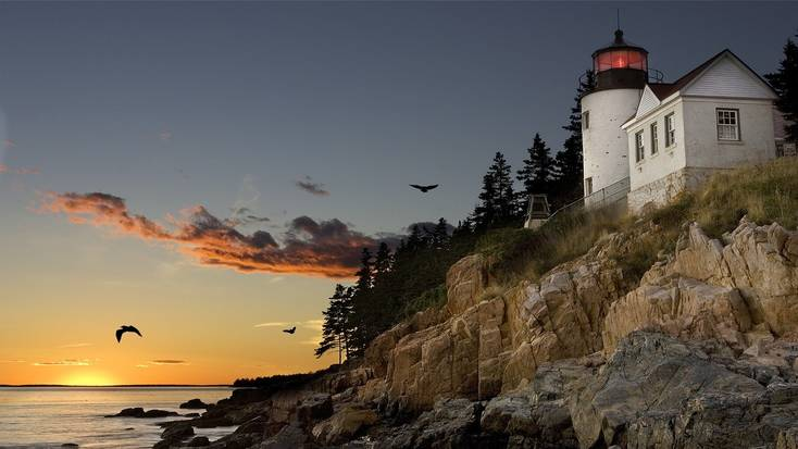 A light house in Maine on a rocky coastline at sun set.