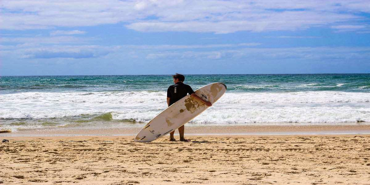 Man standing on beach with surf board on Australia Day 2020, ready for the rest of the day's festivities.