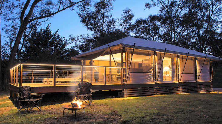 A safari tent illuminated at dusk in the Blue Mountains, NSW.