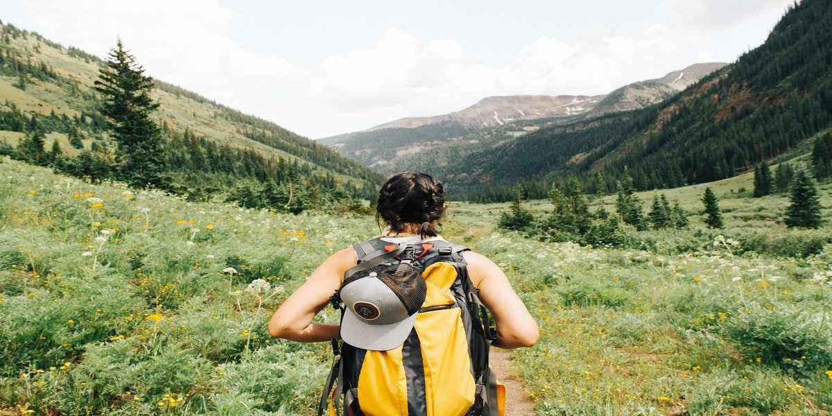 A woman with a yellow hiking pack walking through a green valley.
