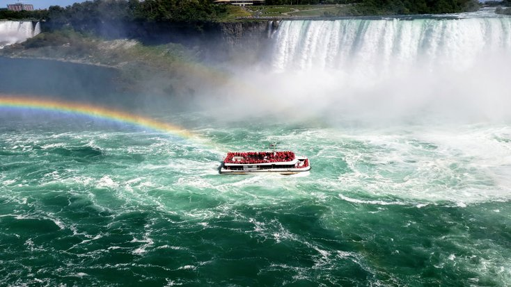 One of the best natural wonders in New York State, a boat full of people visit the Niagara Falls together.