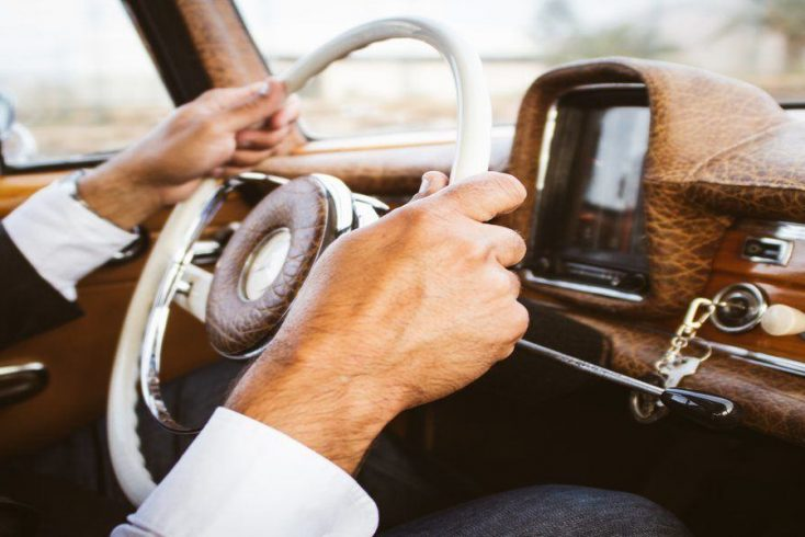 Newlywed holding steering wheel in car on way to his romantic holiday for honeymoon.