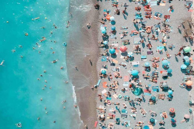 A aerial shot of a beach with people on the sand and in the water.