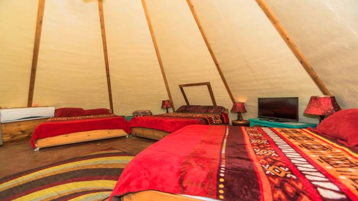 Three queen-size beds in one of the tipi rentals