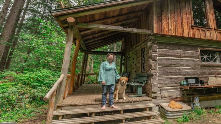 One of our female hosts, Catherine, outside her cabin with her dog