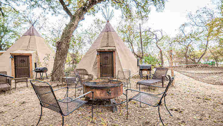 An outdoor seating area with a fire pit and barbecue in front of a tipi rental