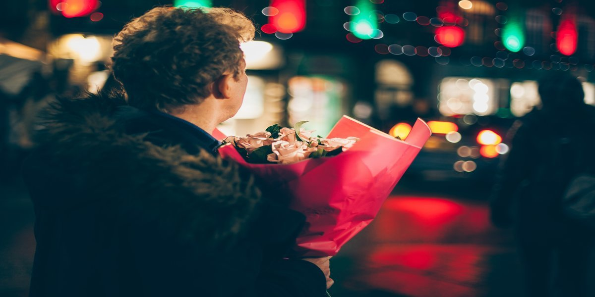 A man at night holding roses for Valentine's Day