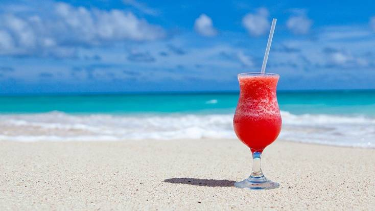 Relax by the sea with a cocktail when you book the best summer vacations