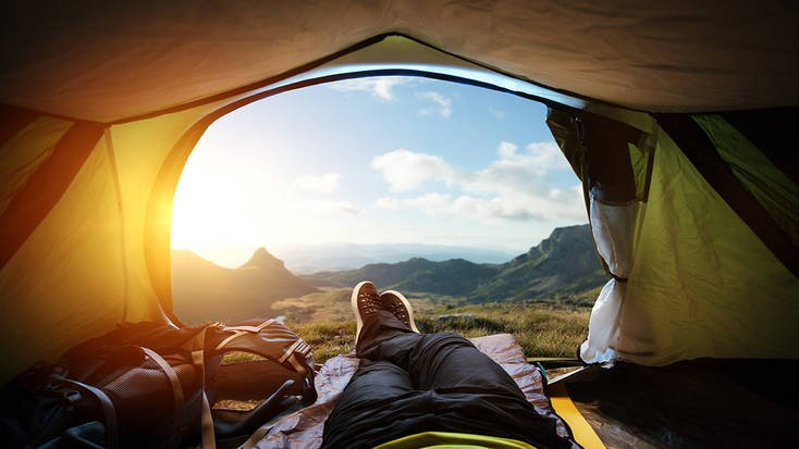 View from the tent on a beautiful mountain landscape. Traveler's legs are crossed in, backpack is laying on the left side of him. Tent is open. Beautiful mountain landscape on background, the bright sun's rays in the upper left corner of image.