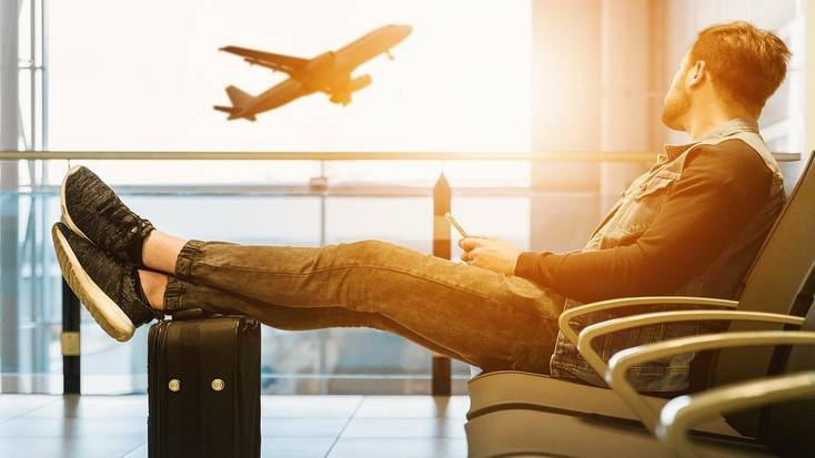 A traveler sitting in an airport watching a plane take off
