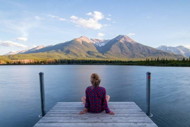 A girl sitting on a jetty looking out over a lake