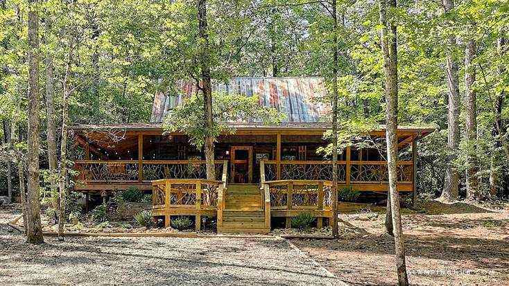 A secluded cabin in the woods with two front decks