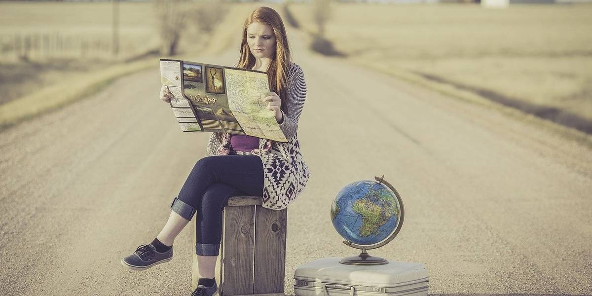 A woman sitting on a suitcase planning a trip post travel restrictions