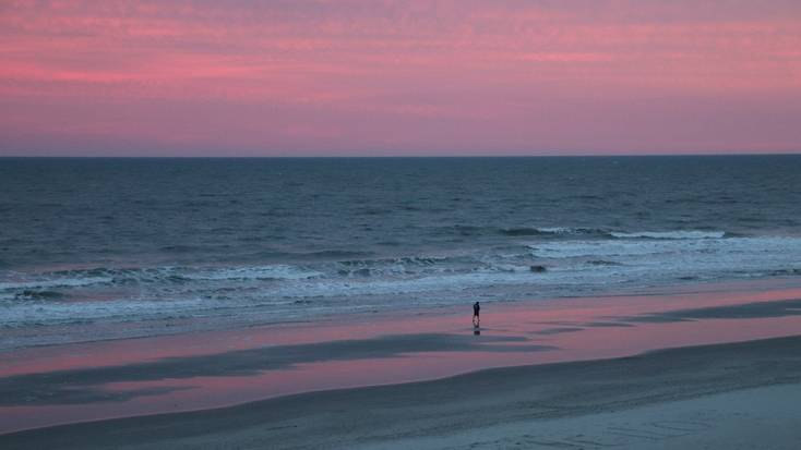 A person walking along Myrtle Beach at sunset
