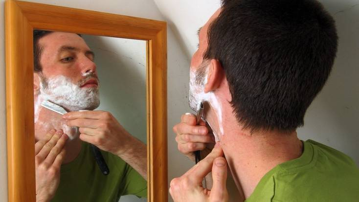 A man shaving in front of the mirror