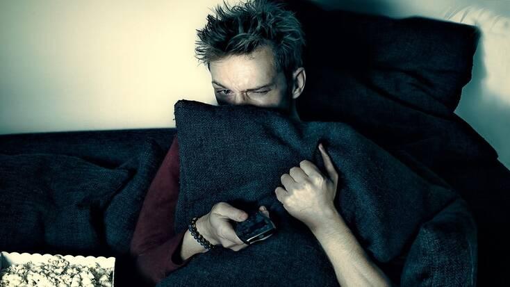 A man watching horror movies while hiding behind a cushion