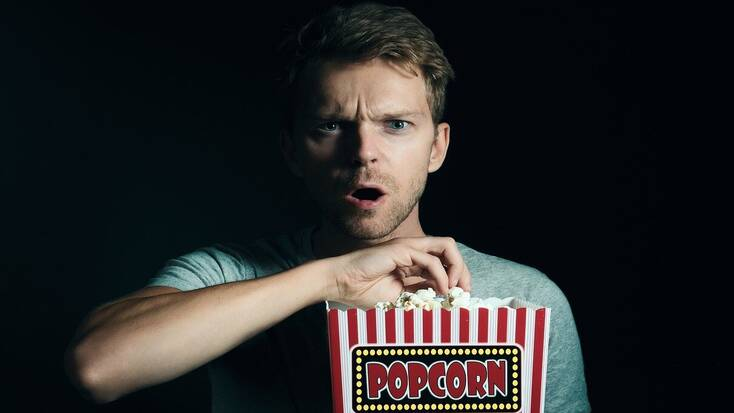 A movie goer eating popcorn