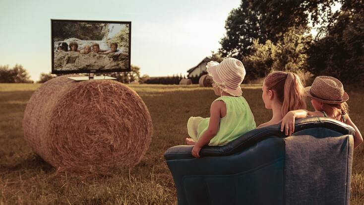 Kids watching tv on a hay bale