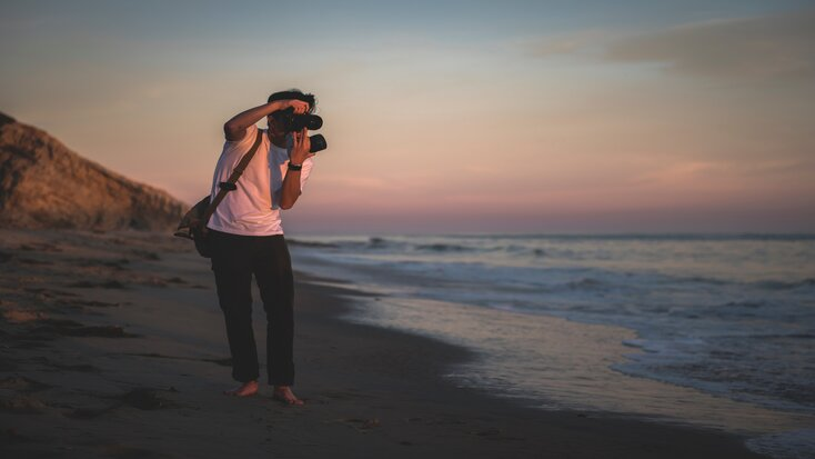 best cameras and accessories and man with them on beach