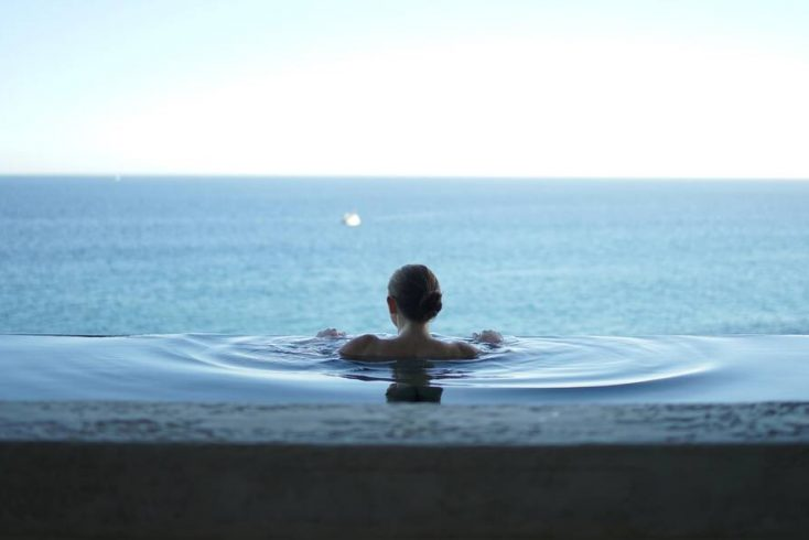 A woman in an infinity pool enjoying the best vacations in Mexico