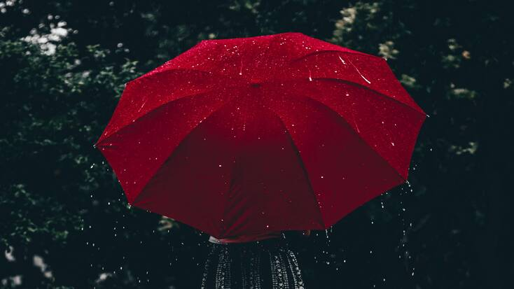 A woman with a red umbrella in the rain