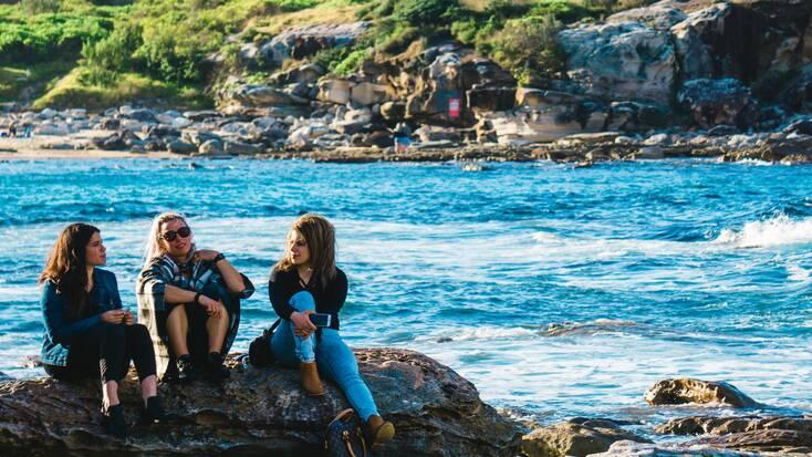 Three women  by the sea on a girls' getaway