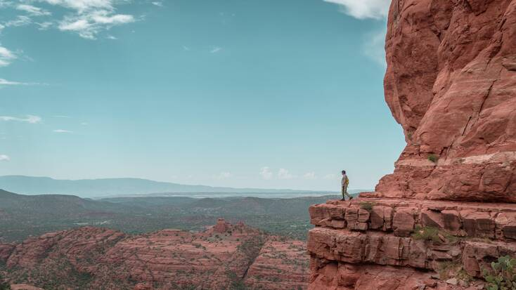 A hiker enjoying views after completing one of the Sedona hiking trails in one of the best spring break destinations