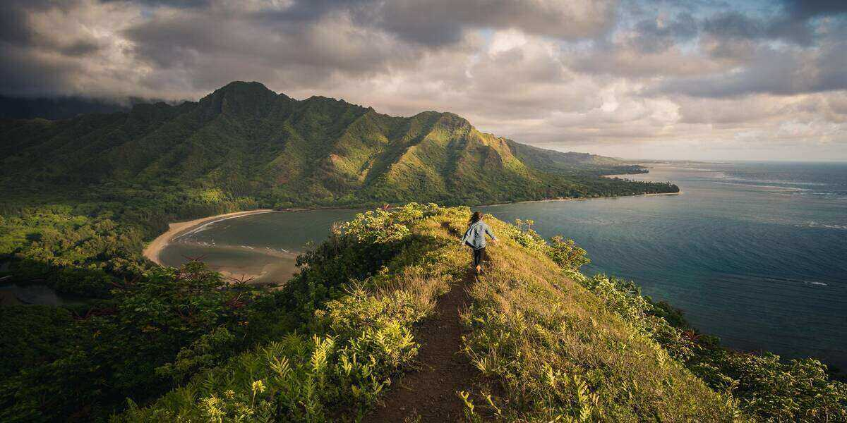 A woman walking over a mountain towards one of the best beaches in Hawaii
