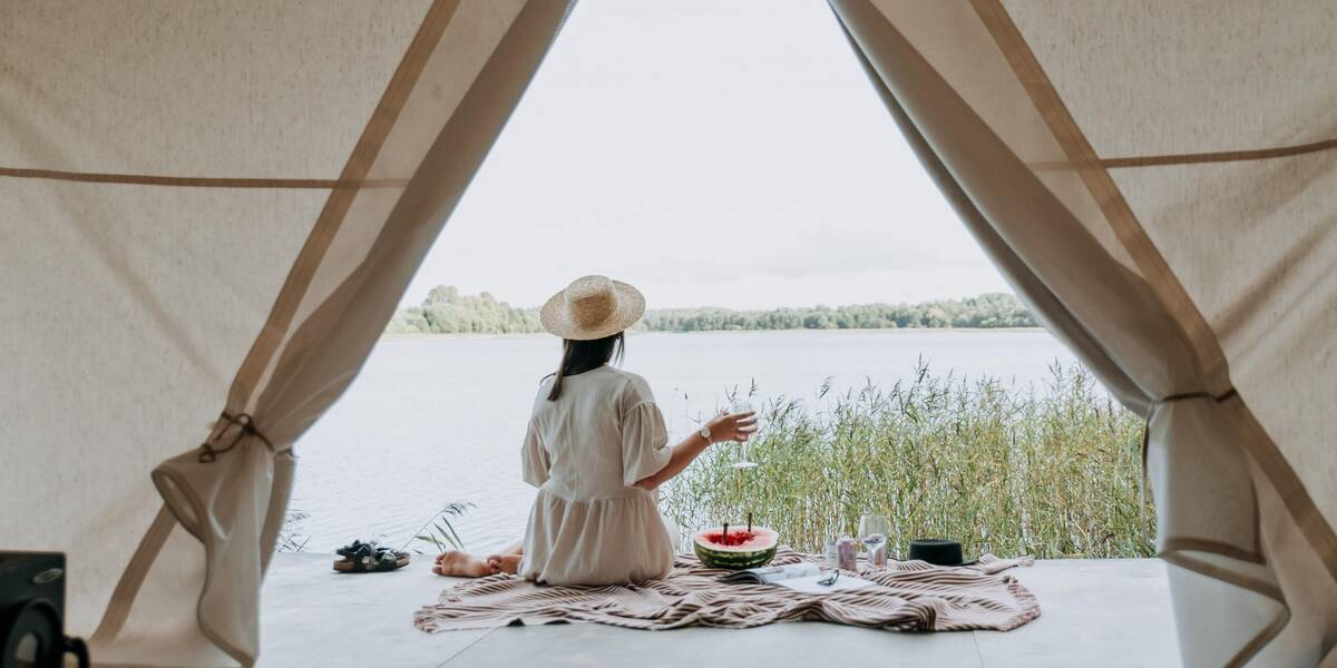 A traveler enjoying views of a lake from her glamping tent in secluded vacation spots