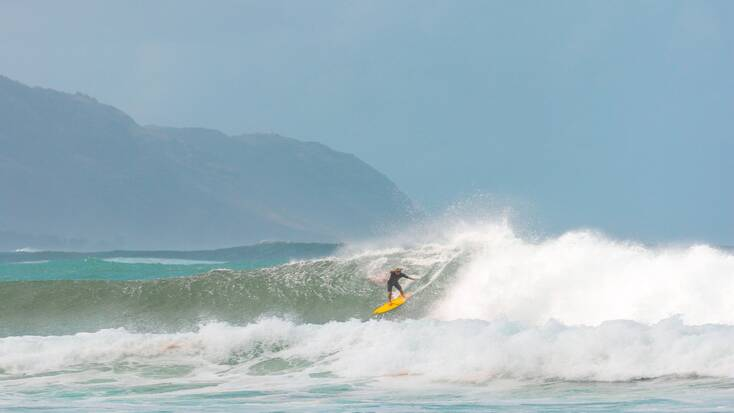 A traveler surfing a wave in Hawaii