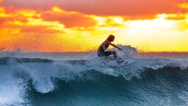 A surfer dude surfing a wave in the sunset