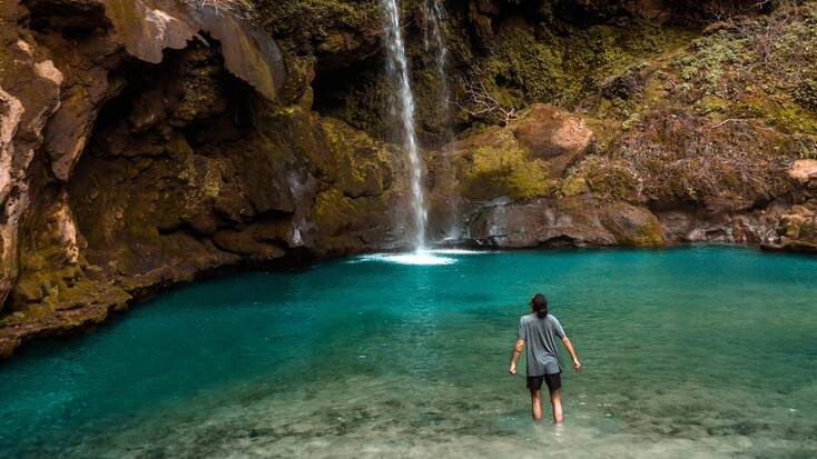 A traveler in a pool with a waterfall, enjoying one of the best spring break destinations