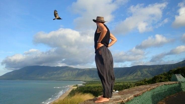 A tourist bird watching exotic birds fly over the ocean