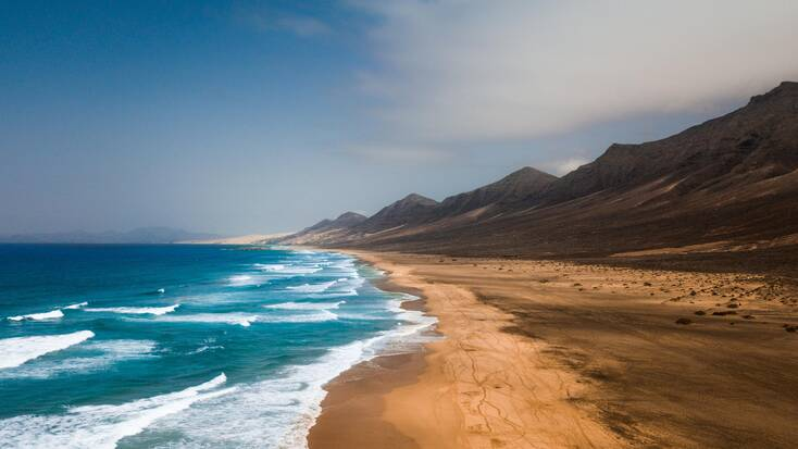 El Cofete Beach, deserted with crystal blue waters and stunning hills in the background