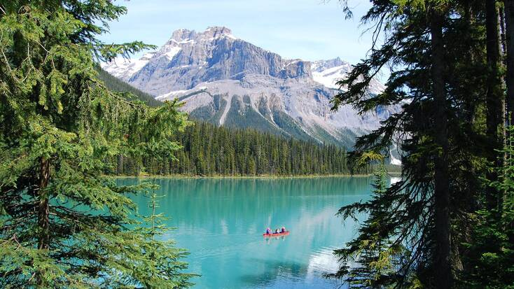 A view of Emerald Lake, BC, with visitors hiking during their vacations in Canada