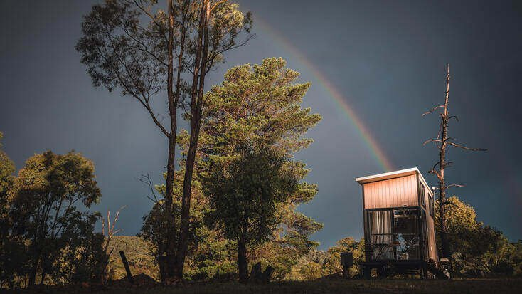 Experience glamping under a rainbow in an Australian tiny house rental.
