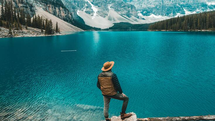 A hiker taking in views of a lake on his Victoria Day vacations in Canada